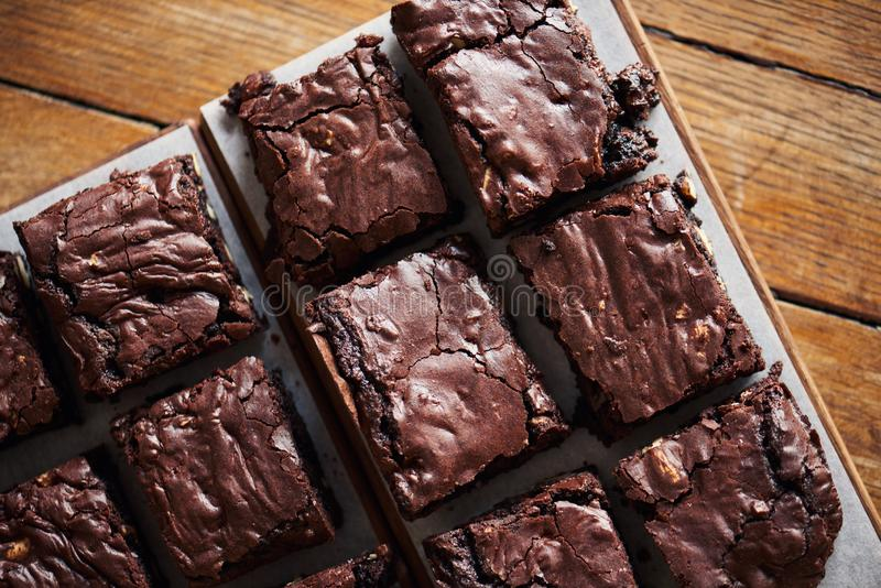 Stacks of homemade chocolate brownies sitting on a cafe table. High angle of a pile of delicious looking freshly made chocolate brownies with nuts sitting on a stock image