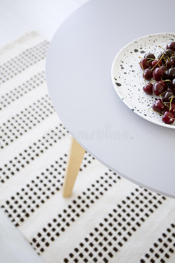 High angle on plate with cherries on grey table in apartment interior with patterned rug. Real photo royalty free stock photography