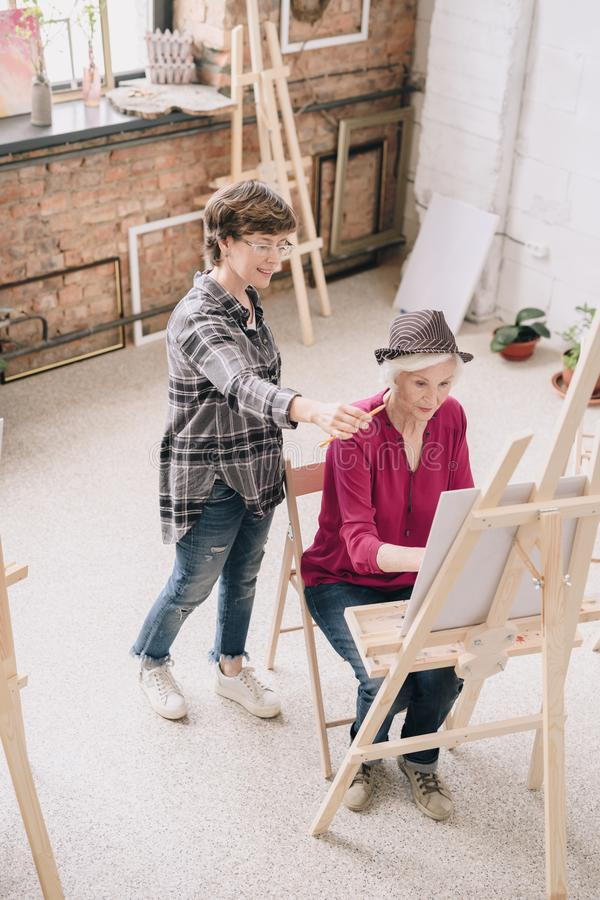 Senior Woman Painting in Art Class. High angle portrait of elegant senior women painting sitting at easel in art studio studying art with smiling female teacher royalty free stock images