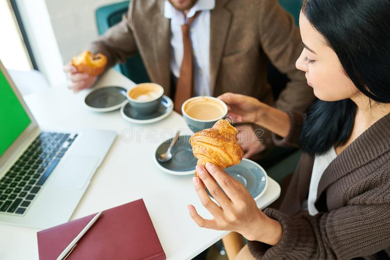 Beautiful Businesswoman Enjoying Coffee with Croissant at Breakf. High angle portrait of pretty young businesswoman sitting at table in cafe and elegantly stock image