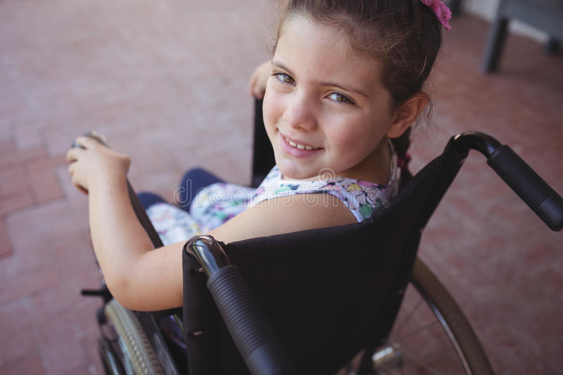 High angle portrait of schoolgirl sitting on wheelchair stock image