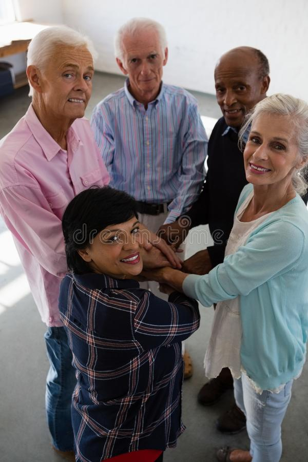 High angle portrait of senior friends stacking hands royalty free stock image