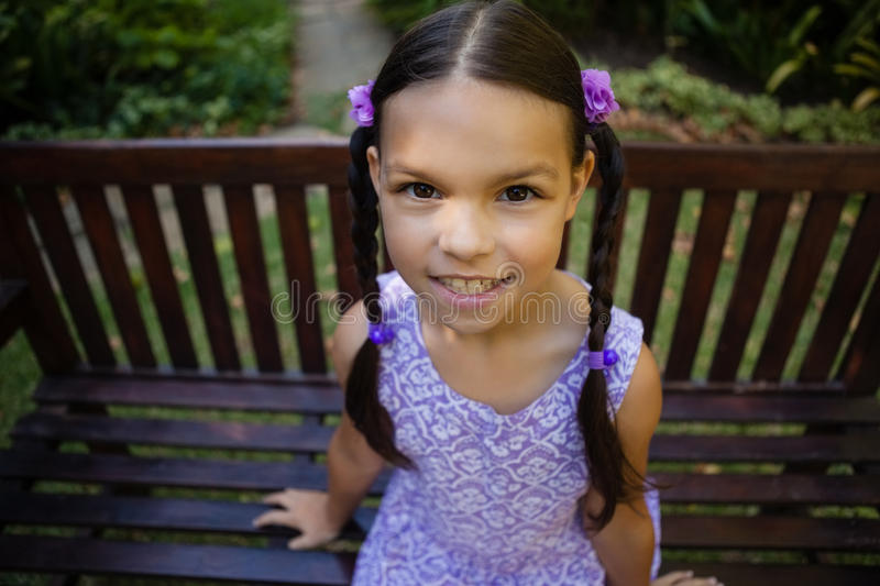 High angle portrait of smiling girl sitting on bench stock photography