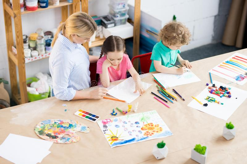 Children Drawing in Art Class. High angle portrait of two children enjoying art and craft lesson with young teacher in development school, copy space stock photos