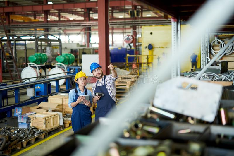 Stock Review in Warehouse. High angle portrait of two modern factory workers, men and woman, wearing hardhats doing inventory standing by shelves in warehouse stock photo