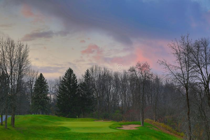 High angle shot of a beautiful golf field with tall trees under the cloudy sky. A high angle shot of a beautiful golf field with tall trees under the cloudy sky stock photos