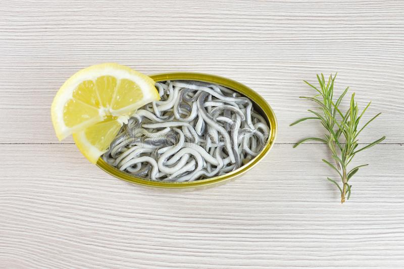 Can of preserved eels. High angle shot of delicious can of preserved eels on on rustic wooden table with lemon royalty free stock image