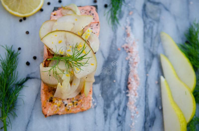 High angle shot of a delicious salmon with slices of pear and lemon on top royalty free stock image