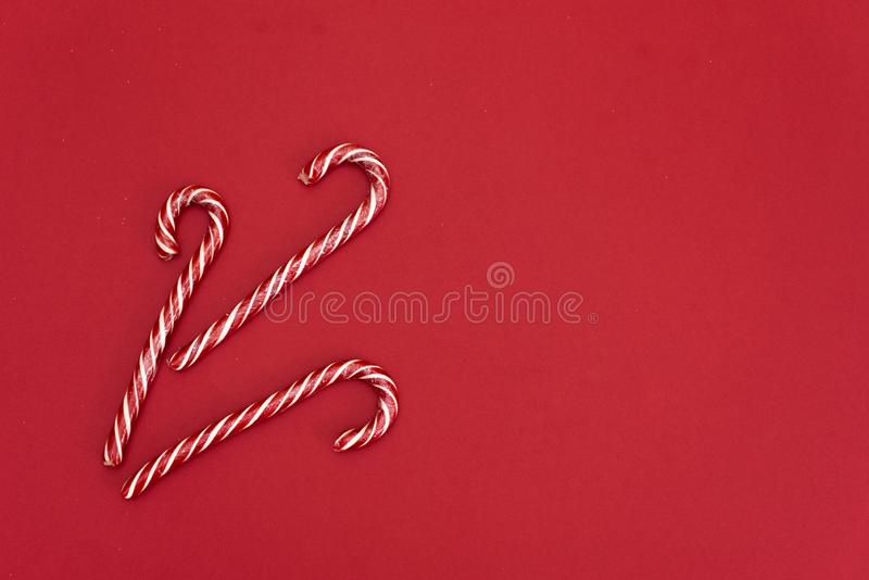 High angle shot of a group of Christmas candy canes on a red background. The peppermint sticks run in all directions and out of stock images
