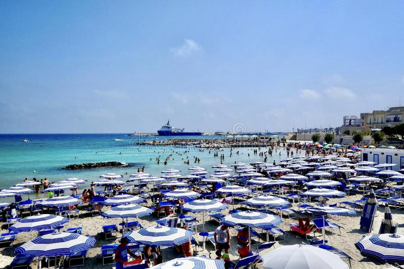 High angle shot of people enjoying the summer at the beach under a blue sky at daytime. A high angle shot of people enjoying the summer at the beach under a blue stock images