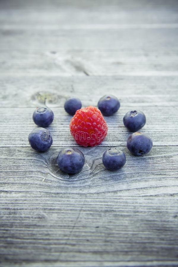 High angle shot of raspberry and blueberries on a wooden surface. A high angle shot of raspberry and blueberries on a wooden surface royalty free stock photography
