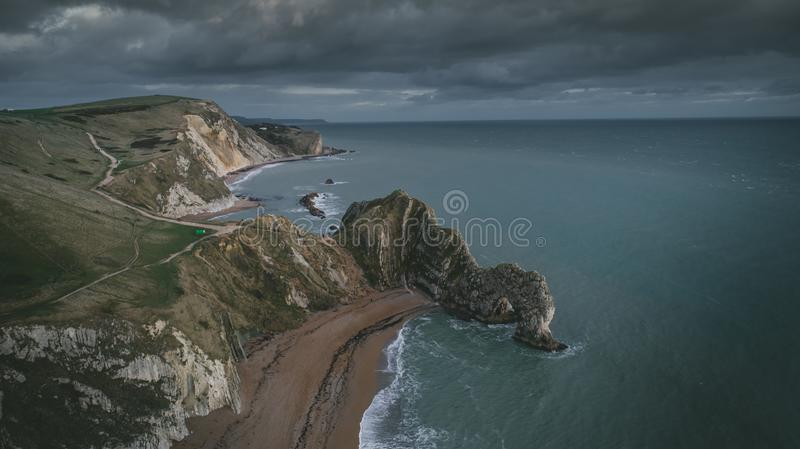 High angle shot of the rocks in the seashore of the Durdle Door in Dorset under the cloudy sky. A high angle shot of the rocks in the seashore of the Durdle Door stock photos