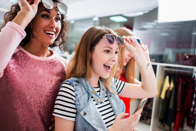 High-angle shot of young stylish female friends wearing trendy sunglasses and clothes having fun in shopping center royalty free stock photos