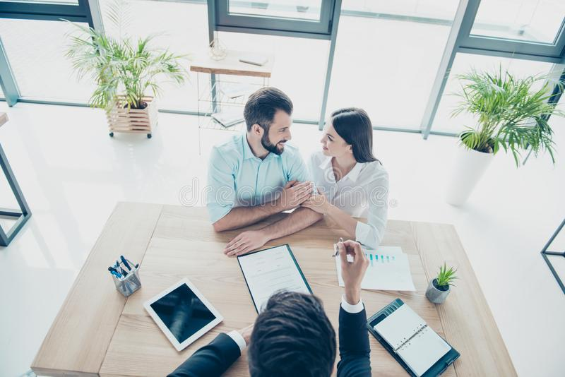 High angle top view of cheerful married couple, getting a car key from a car dealer in the showroom and signing contract, they ar royalty free stock photography