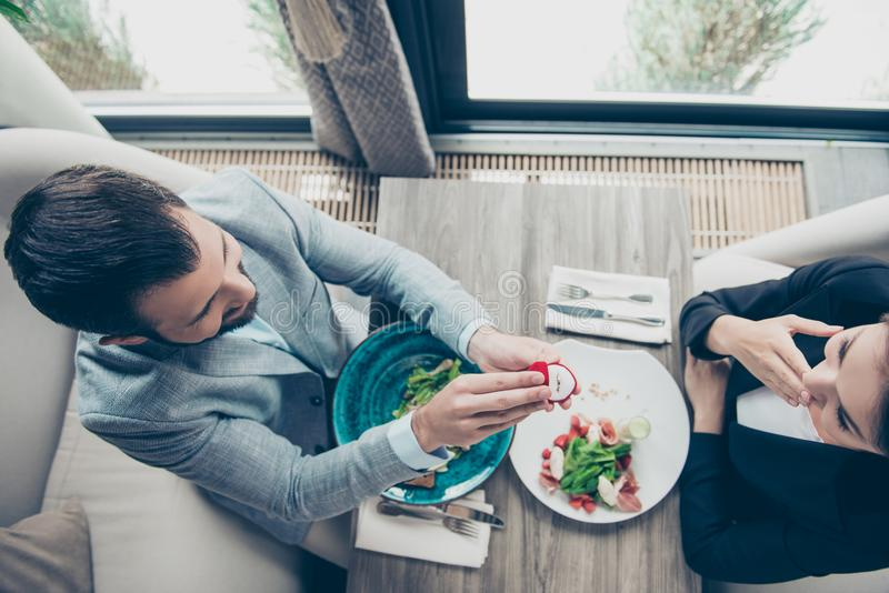 High angle top view of romantic brunet bearded guy, proposing to. His shocked brunette lover, they are in a fancy restaurant, in formal outfits, ordered salads stock photography