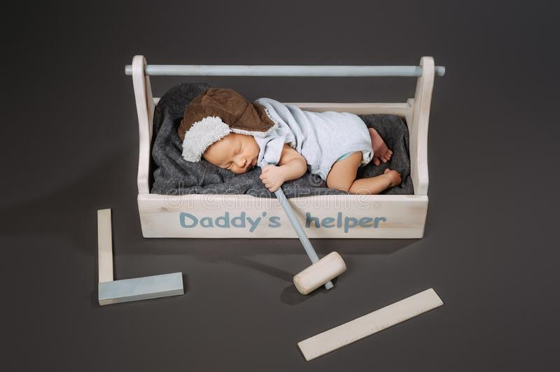 High angle view of adorable baby with hammer in hand sleeping in wooden toolbox with daddys. Helper lettering stock photography