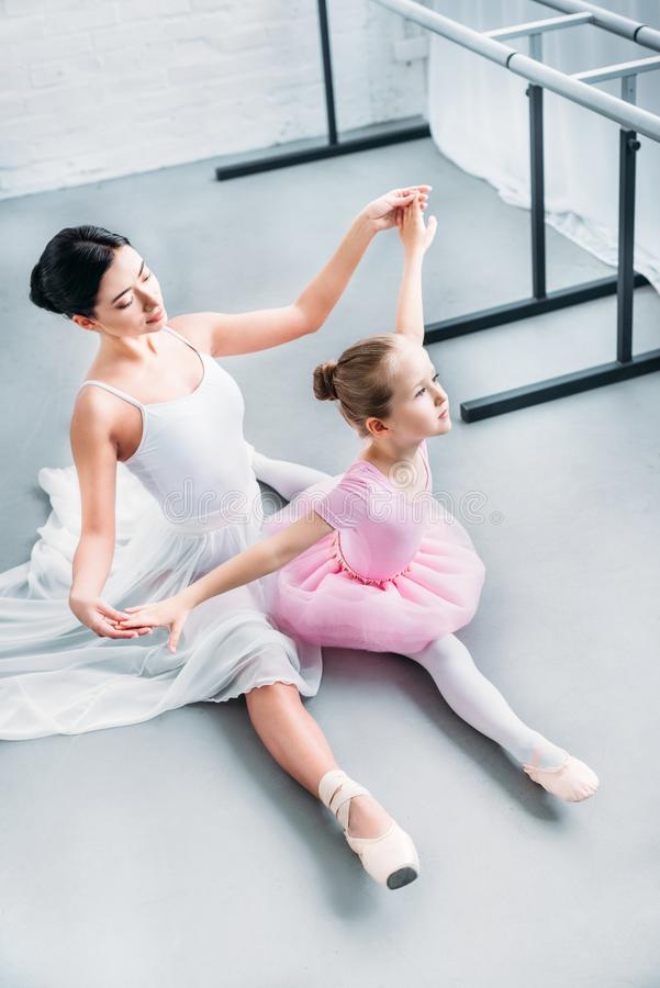 High angle view of adult ballerina exercising with cute little child. In pink tutu in ballet school stock images