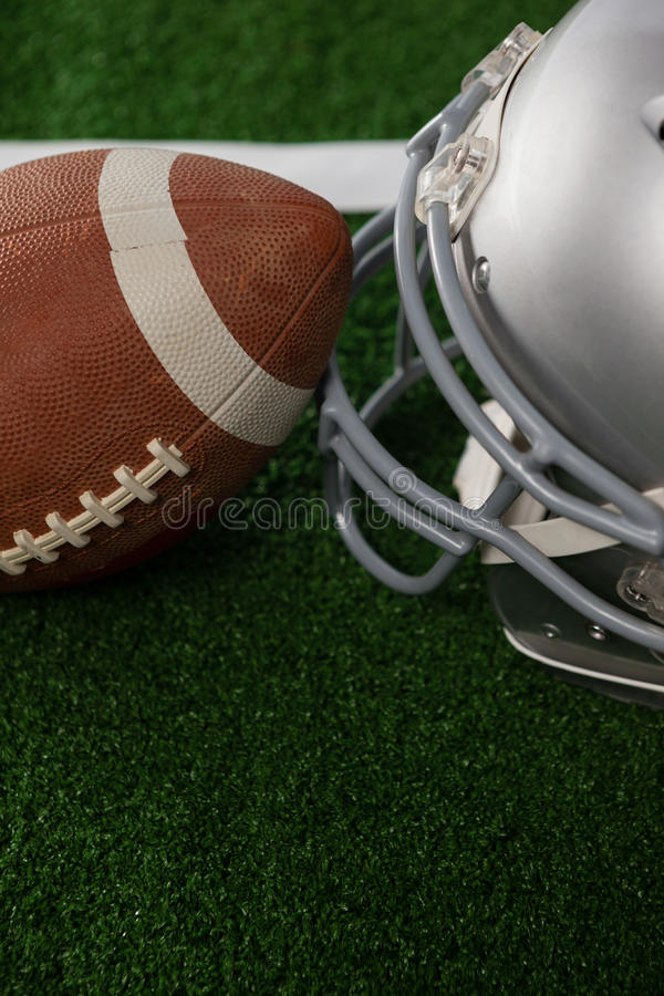 High angle view of American football by sports helmet. On field stock photography