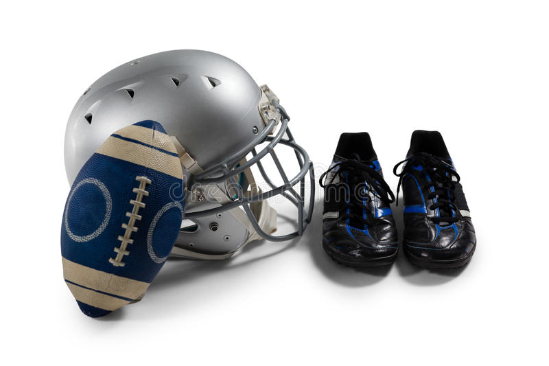 High angle view of American football with sports shoes and helmet. Against white background royalty free stock photo