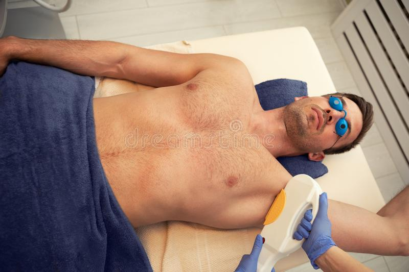 Laser epilation treatment on man`s armpit royalty free stock photo