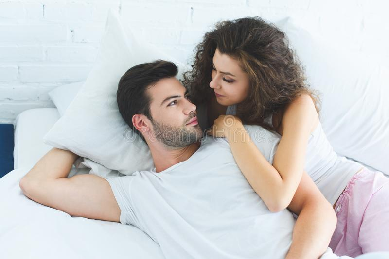 High angle view of beautiful young couple in love lying in bed and looking. At each other royalty free stock photos