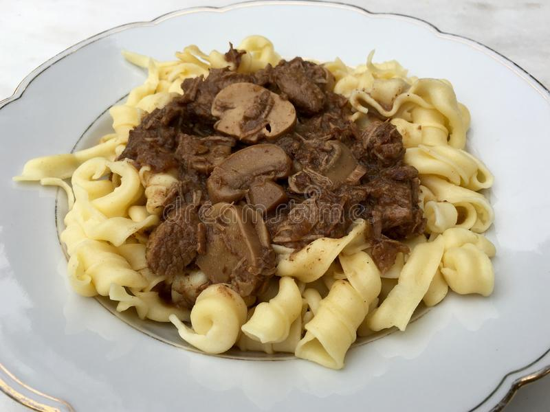 High angle view of beef goulash with mushrooms and noodles served on white plate royalty free stock photos