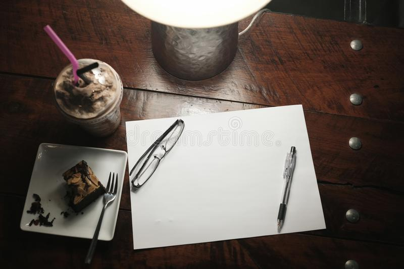 Top view of blank paper with stationery and dessert food on wooden background selective focus. Break time and chilling royalty free stock image