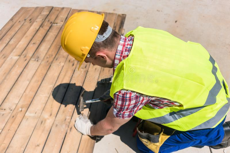 High-angle view of a blue-collar worker using a hammer on the co stock photo