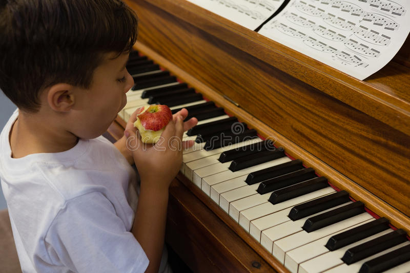 High angle view of boy eating apple while sitting by piano. At home stock photo