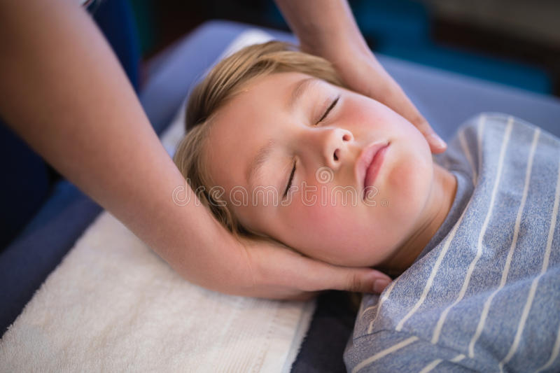 High angle view of boy with eyes closed receiving neck massage from female therapist. At hospital ward royalty free stock photography