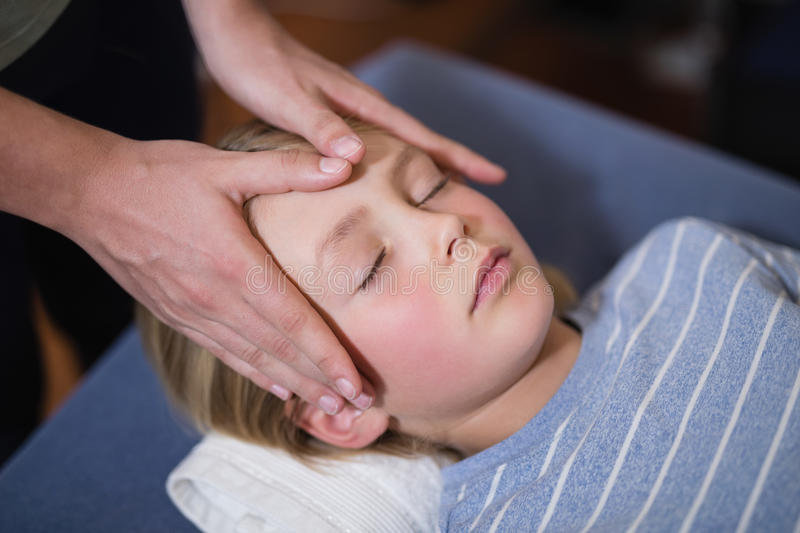 High angle view of boy lying with eyes closed receiving head massage from female therapist stock photos