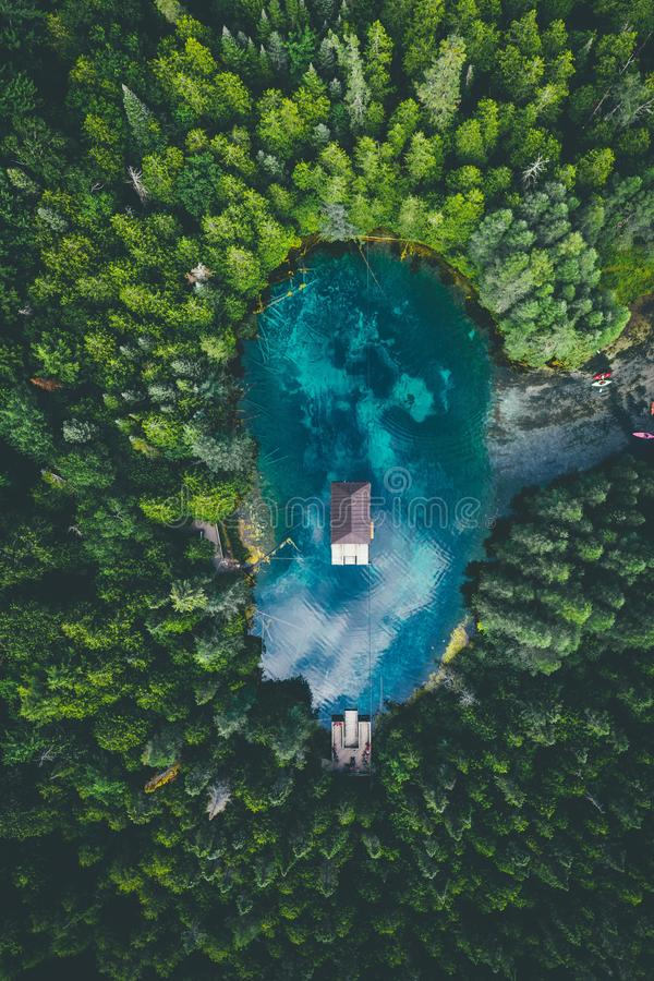 High angle view of a building in a lake surrounded by forests under a cloudy sky. A high angle view of a building in a lake surrounded by forests under a cloudy stock photo