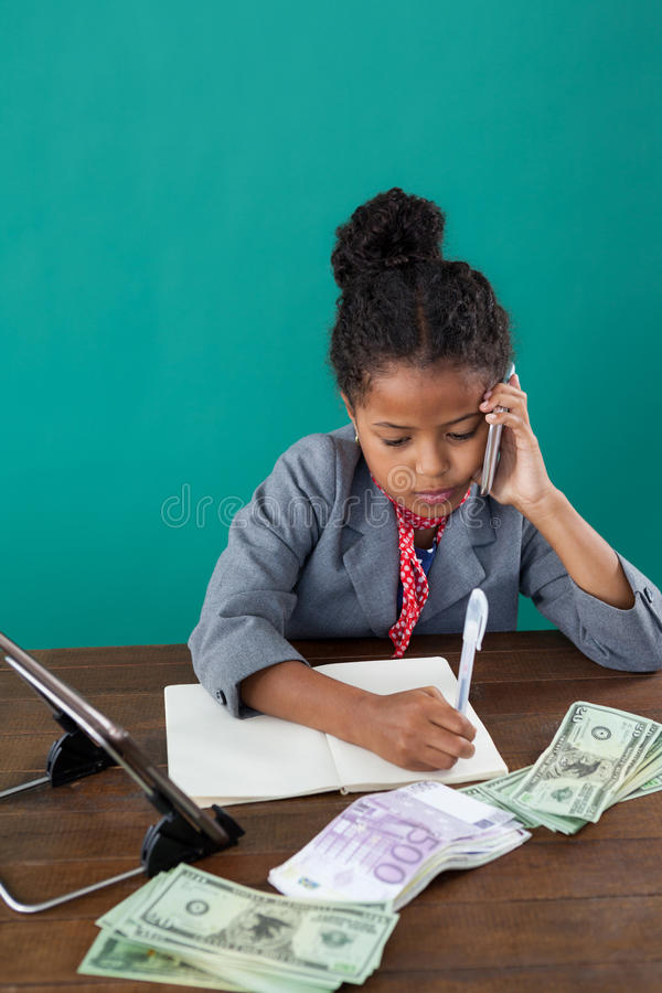 High angle view of businesswoman using phone while writing on book by paper currency stock image
