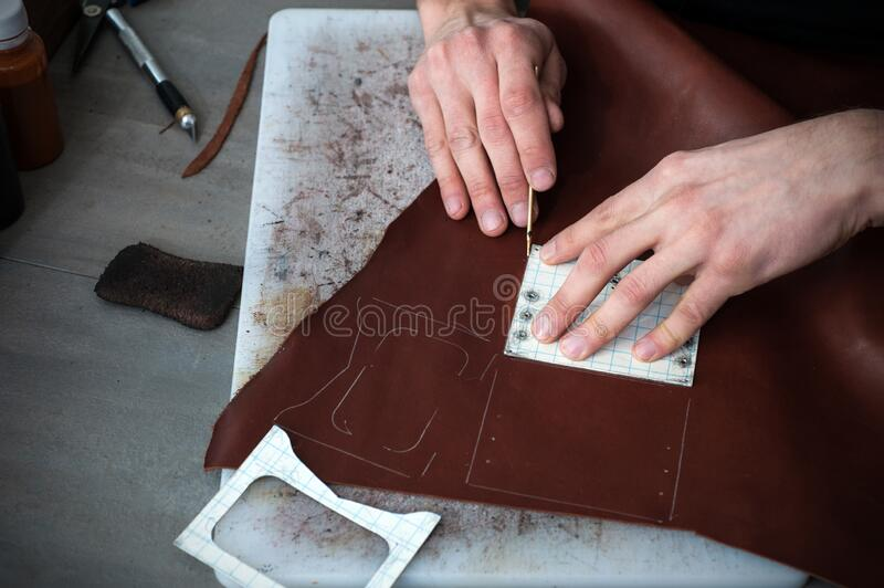 Male hands of master cutting with a knife pattern from genuine leather. Hand-made leather goods manufacturing. Small business. High angle view of caucasian male royalty free stock photos