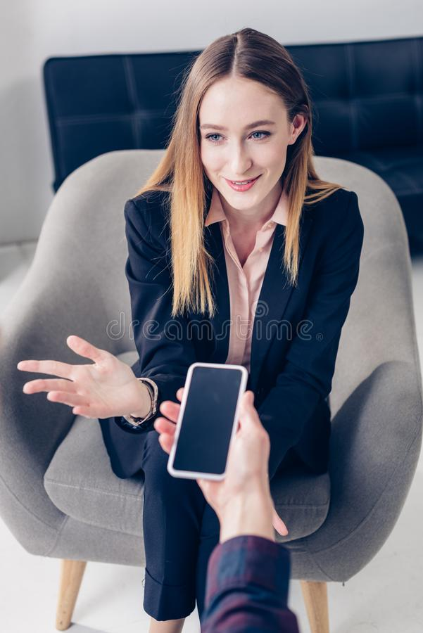 High angle view of cheerful businesswoman in suit giving interview to journalist. In office stock image