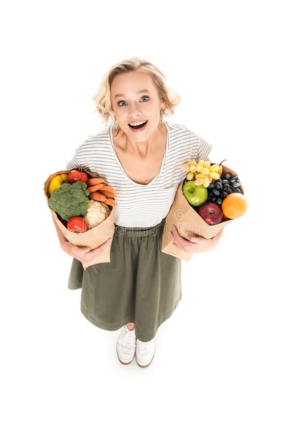 high angle view of cheerful young woman smiling at camera while standing with paper bags full of fresh fruits and vegetables stock images