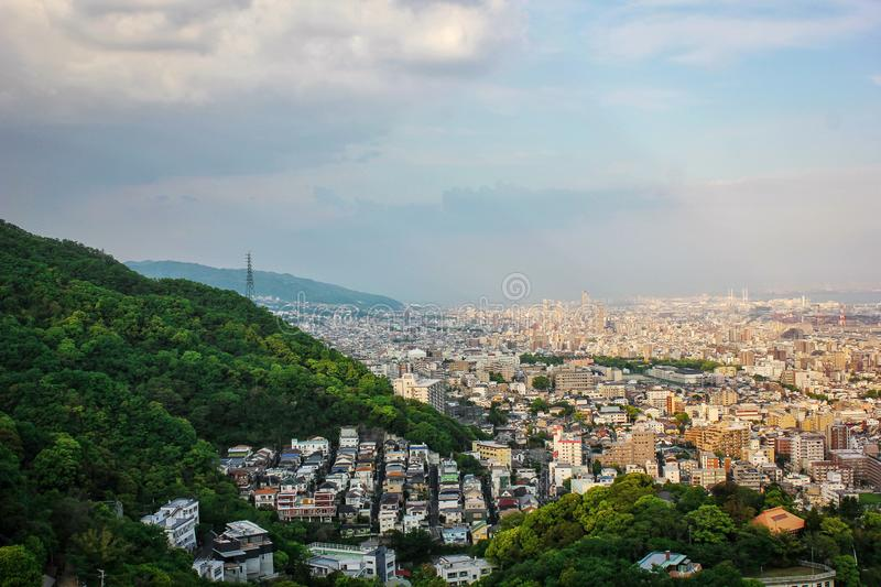 High angle view of cityscape of Kobe Japan, crowded with houses and building next to mountain of trees royalty free stock photo