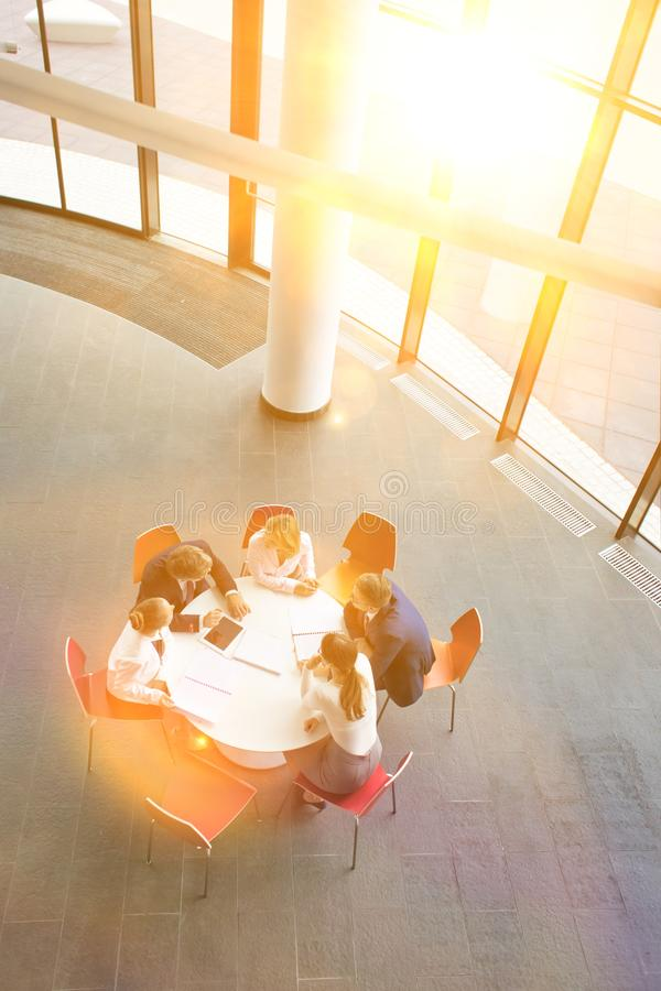 High angle view of colleagues planning while sitting during meeting at office royalty free stock image