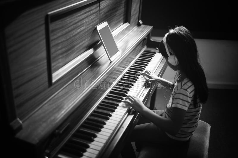 High angle view of concentrated girl practicing piano. High angle view of concentrated girl wearing headphones while practicing piano in classroom at music royalty free stock images
