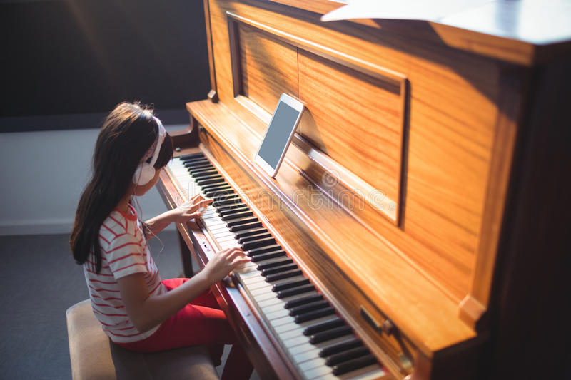 High angle view of concentrated girl practicing piano stock photography