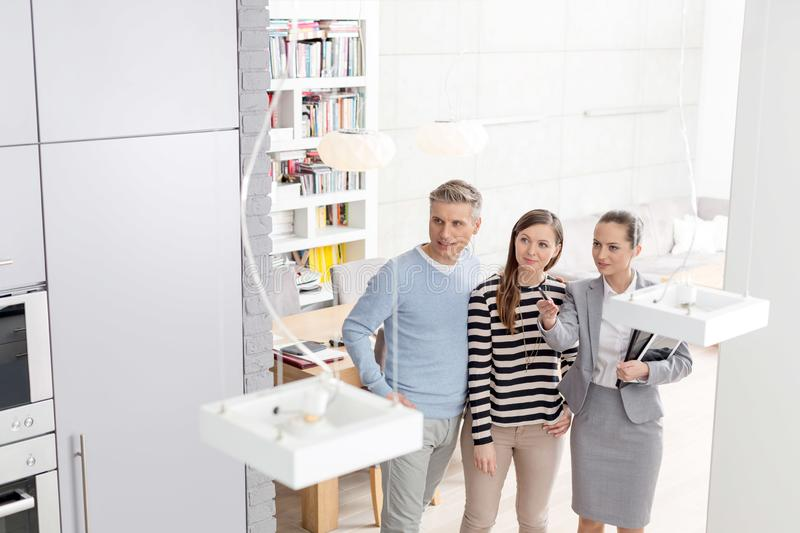 High angle view of confident saleswoman gesturing to couple while standing in apartment stock images