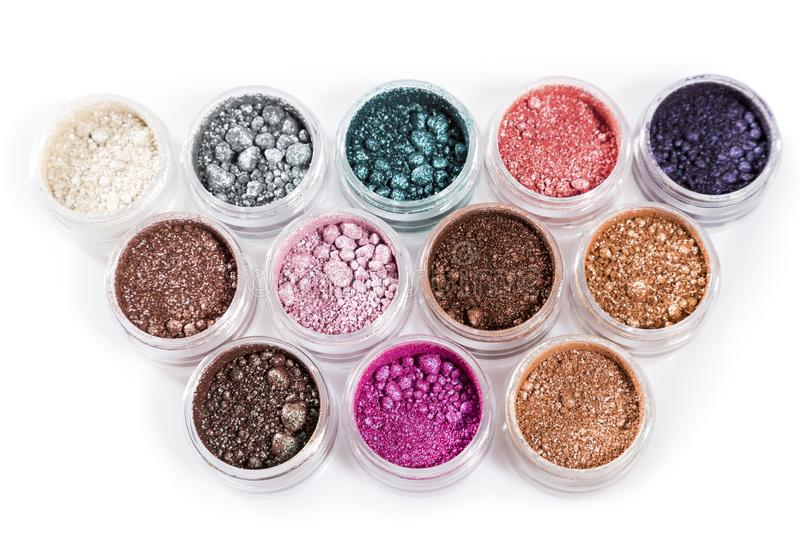 High angle view of cosmetic powders in jars. Close up high angle view of a dozen jarred cosmetic powders in varied colors against a white background stock image