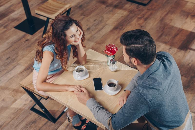 high angle view of couple holding hands while having date royalty free stock photo