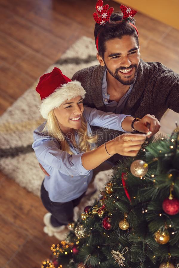 Couple decorating Christmas tree. High angle view of couple in love, wearing Santa hats, decorating Christmas tree and having fun at home on Christmas morning stock images