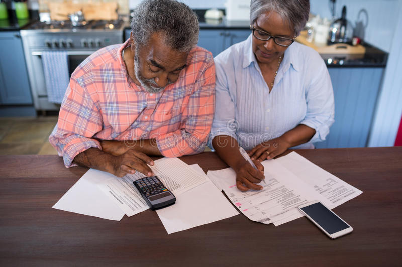 High angle view of couple using calculator stock photo