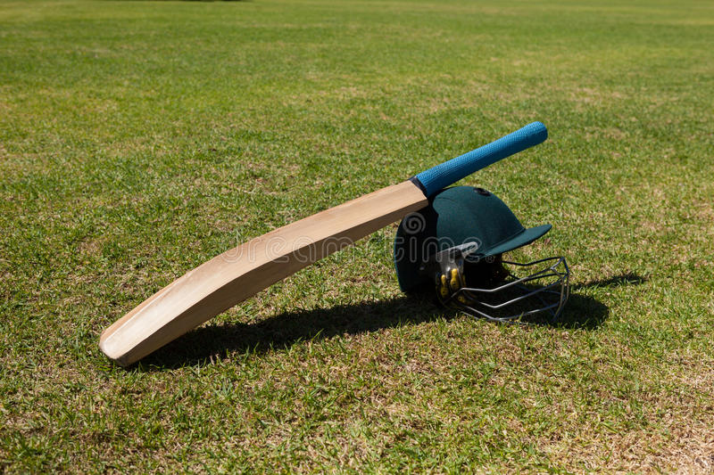 High angle view of cricket bat and helmet on field. During sunny day royalty free stock photos