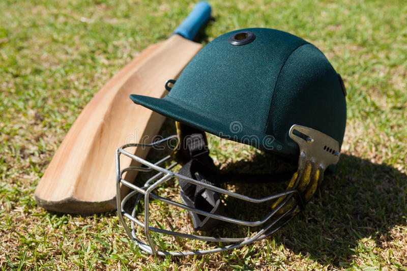 High angle view of cricket helmet and bat on field. During sunny day royalty free stock image