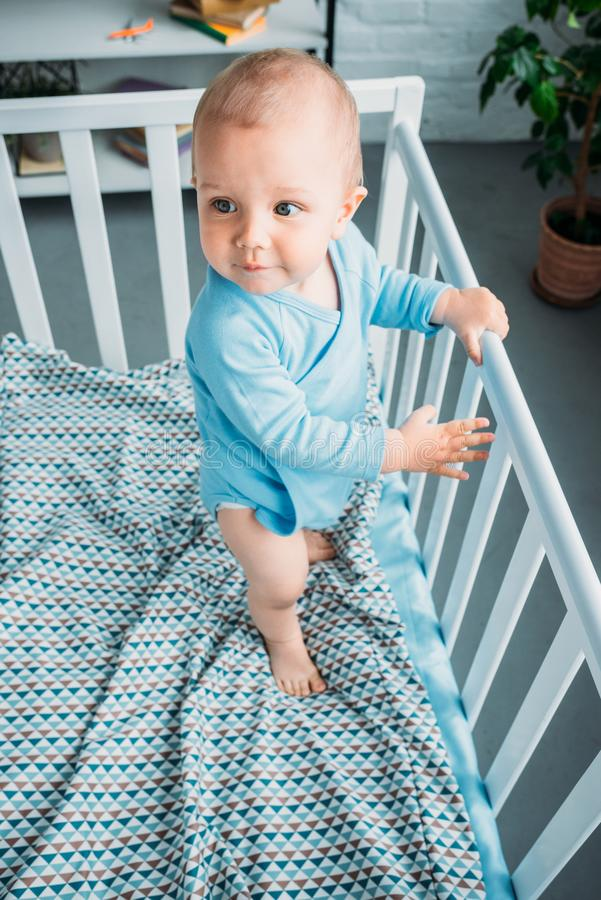 High angle view of cute little baby standing. In crib stock photos