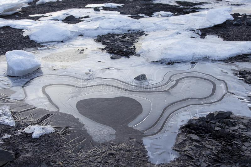 High angle view of detail of ice melting and forming whorl patterns on rocky beach. In late winter, St. Lawrence river bank, Cap-Rouge, area, Quebec City stock photos