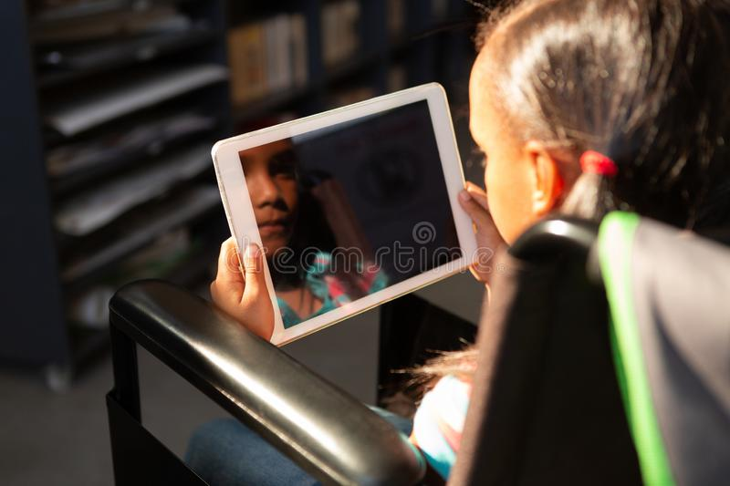 Disabled schoolgirl using digital tablet in the library stock images